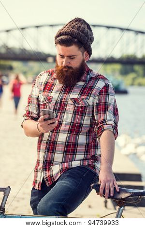 Trendy hipster young man with bicycle using smart phone. Posing next to river