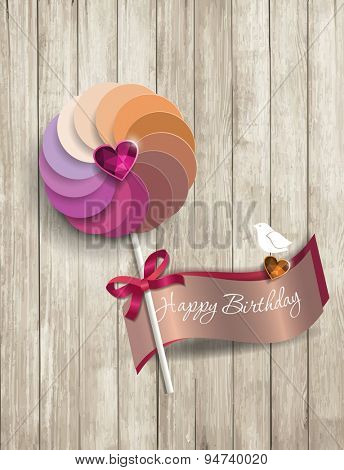 happy birthday text on wooden texture with paper lolipop
