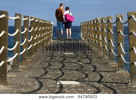 Young couple walking on a ocean pier