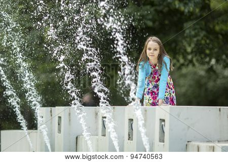 Little cute girl sitting on a public fountain.