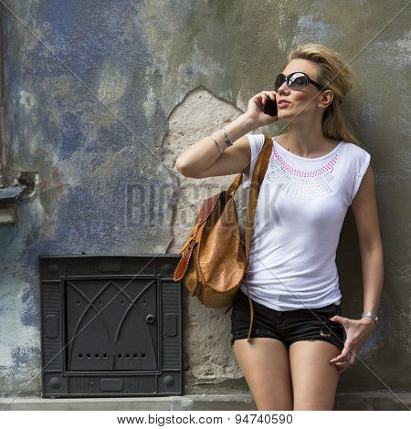 Young attractive woman talking on the phone standing on the street of the old town.