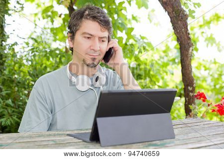 young man at the phone and tablet pc with headphones, outdoor