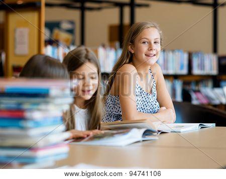 Little girls reading books in library