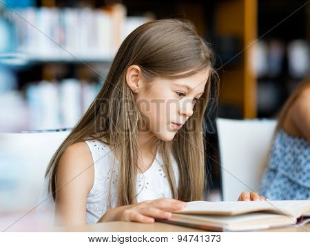 Little girl reading books in library