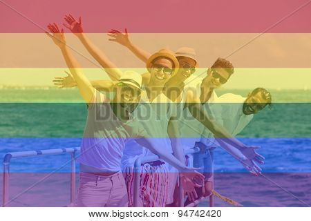Celebrating marriage equality, group of friends at the beach with the LGBT flag overlapped with medium opacity.