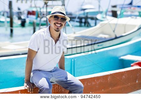 Young man at the beach wearing casual clothing, sitting on a boat. Isla Mujeres, Cancun, Mexico.