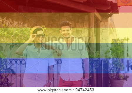 Celebrating marriage equality, fashionable male couple at the beach with the LGBT flag overlapped with medium opacity.