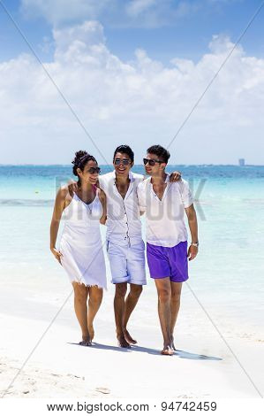Group of friends in an empty beach in the Caribbean. Isla Mujeres, Cancun, Mexico.