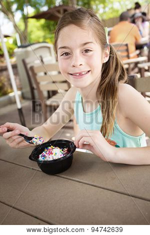 Cute smiling little girl eating a delicious bowl of ice cream at an outdoor cafe