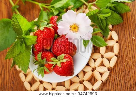 several strawberries on a plate on a table with a flower and mint. close-up