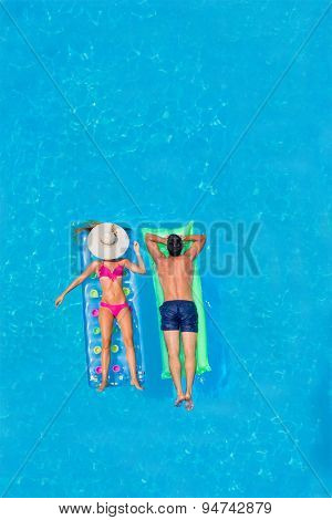 Couple on lilos Relaxing in a pool