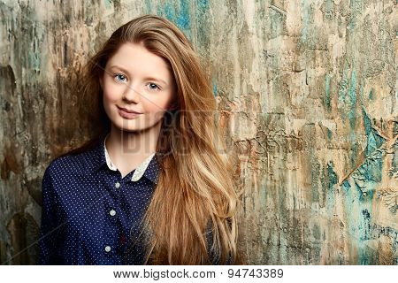 Portrait of a cute smiling teen girl standing by the grunge wall.