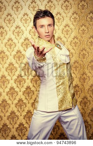 Portrait of a handsome man ballet dancer in a stage costume. Show-ballet. Golden vintage background.