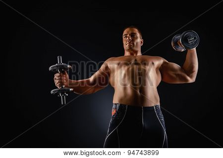 Handsome muscular man posing with dumbbells over black background. Bodybuilding. Professional sports.