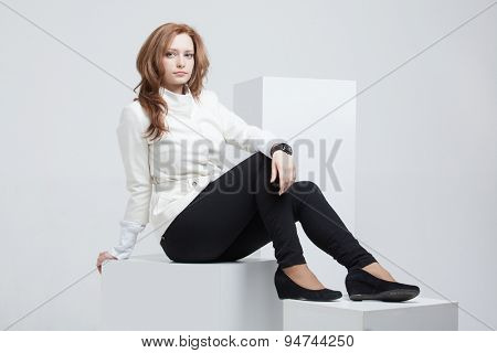 young woman sitting on white cubes