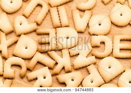 Baked word biscuit over wooden table