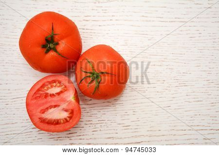 Top view of three fresh tomatoes on a white wooden table with copy-space