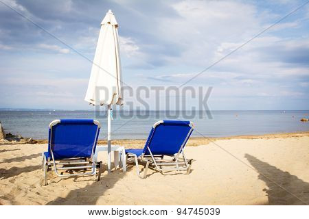 Two chairs and umbrella on the beach in the morning