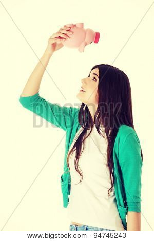 Young happy woman holding piggybank