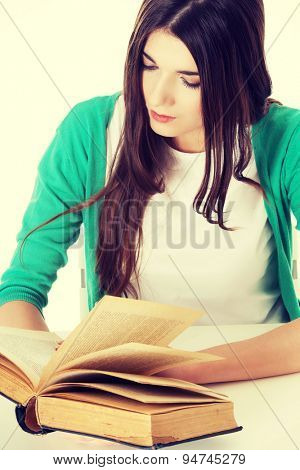 Pretty teenager reading interesting book