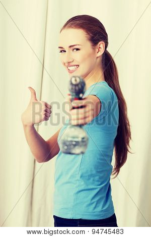 Young woman with a power drill