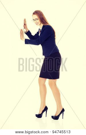 Beautiful businesswoman trying to push the wall