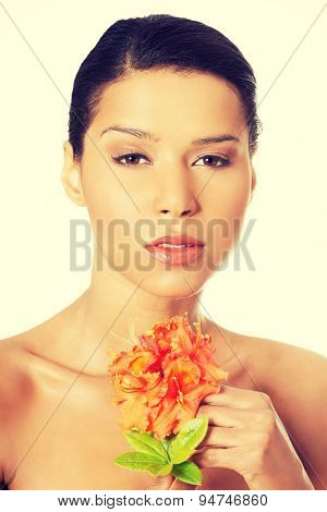 Young beautiful woman with a flower in spa