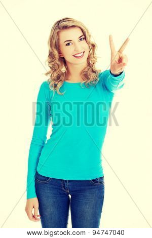 Young woman showing two fingers,victory sign, positive or peace gesture