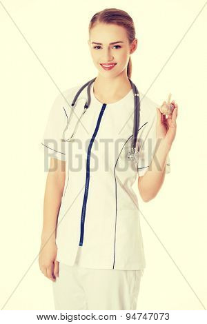 Female doctor in uniform holding garlic