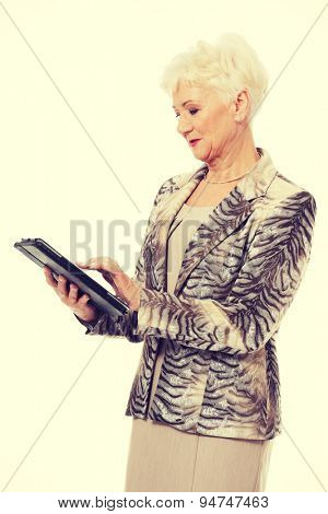 Happy senior woman using a tablet