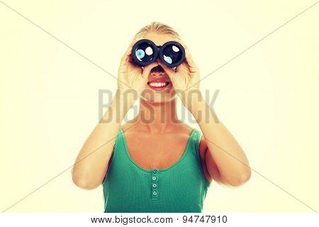 Happy woman looking through the binocular
