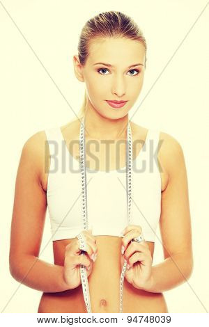 Young slim woman holding measure