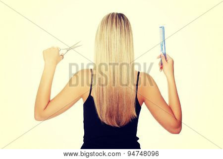 Woman with long hair holding comb and scissors