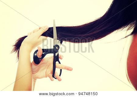 Young angry woman cutting hair