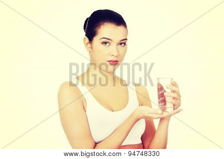 Young healthy woman holding glass of water