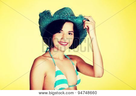 Young slim woman in swimsuit holding a hat