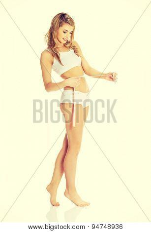Beautiful woman measuring, wearing underwear