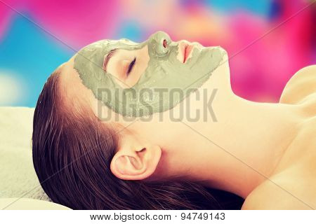 Young woman in spa with a mask on her face