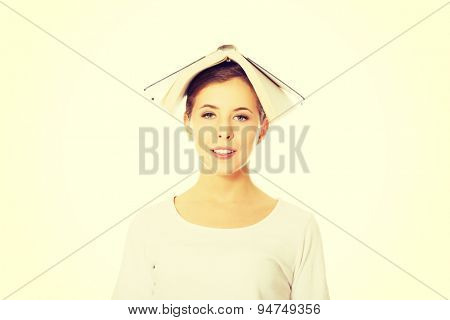 Woman smiling holding book on head