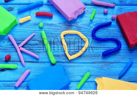 modelling clay of different colors forming the word kids on a blue wooden surface