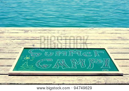 the text summer camp written with chalk of different colors in a chalkboard, on a wooden pier on the sea, heavy processing for retro bleached look