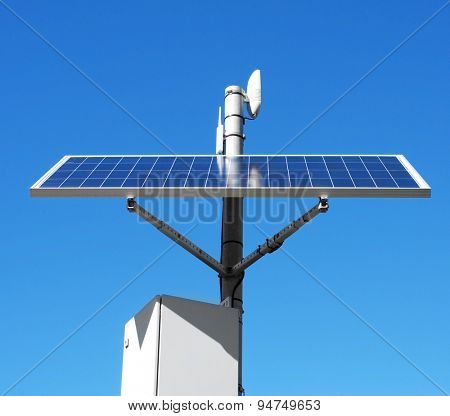 closeup of a solar panel installed in the top of a pole, over the blue sky