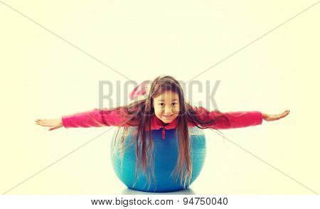 Little girl lying on a big ball