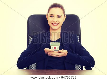 Happy attractive businesswoman, real estate agent, holding a house model
