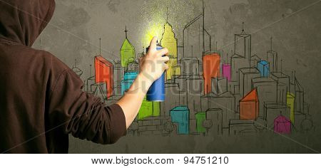 Young urban painter drawing colorful city  on the wall