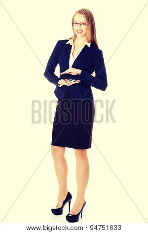 Beautiful businesswoman holding a model of car