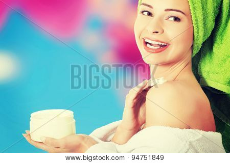Happy woman applying cream on shoulders