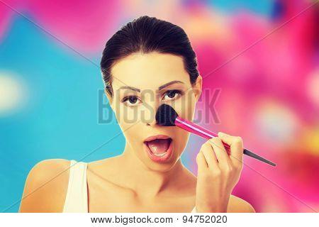 Attractive woman applying make up