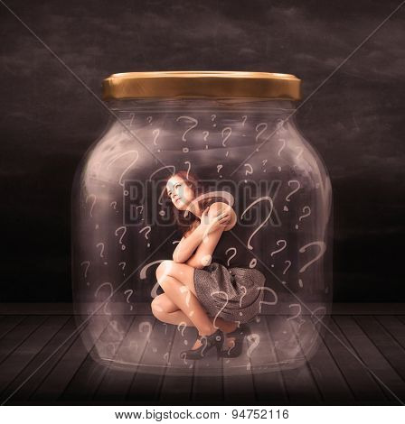 Businesswoman locked into a jar with question marks concept on background