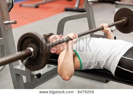 Muscular Young Man Using Weightlifting Lying In A Fitness Centre